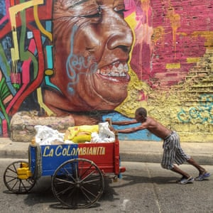 A man wheels concrete in a push cart in Cartagena.