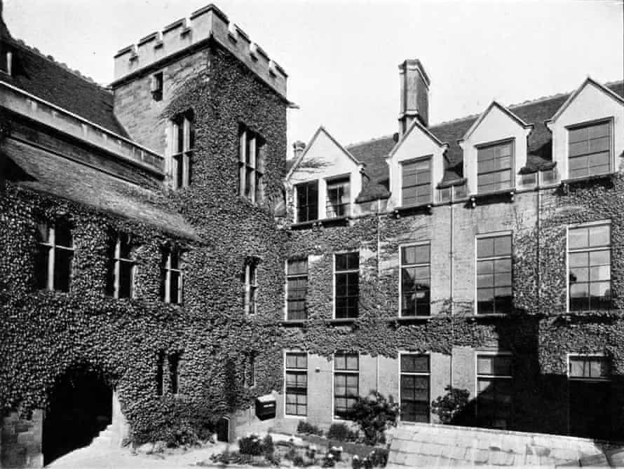 Black and white photograph of Cavendish Laboratory buildings; showing the corner of a courtyard, where two wings meet; there is a three-storey tower at the corner. much of the building is covered in a climbing plant.