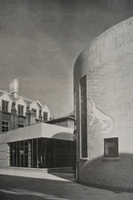 Black and white photograph of the historic Mond laboratory. The lab, to the right of the photo, is curved, with a carving of a crocodile.  A single storey square building is to the left, with a wraparound window covering most of the visible walls.