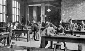 Black and white photograph of the inside of a large, high-ceilinged brick building.  Lights hang down from long chains over wooden tables where students – mostly male – in Edwardian suits and coats, examine technical equipment.  Two possibly female figures can also be seen.