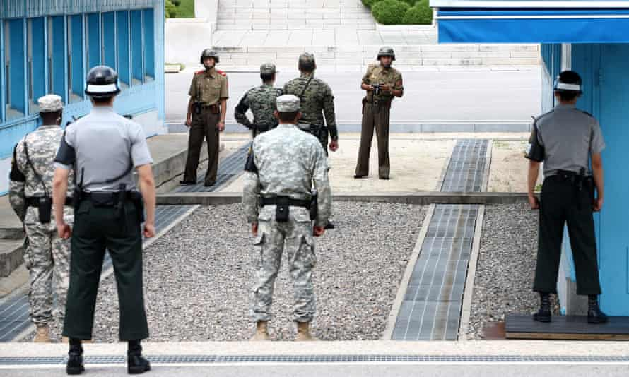 North Korean soldiers look back at their South Korean counterparts soldiers at the military demarcation line in the demilitarised zone (DMZ).