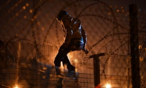 a migrant tries to climb over a security fence in Calais.