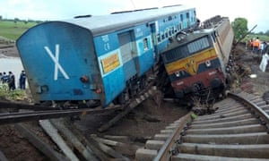 A locomotive and a carriage lie side by side at the crash scene outside Harda in Madhya Pradesh state.