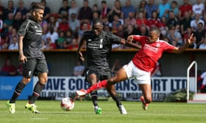 Swindon Town, whose defender Nathan Thompson is here challenging Liverpool's, Christian Benteke in a friendly, should be among the contenders this season.