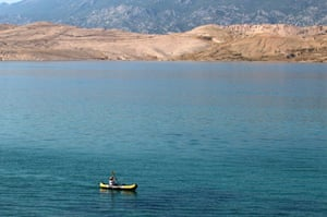Sophie paddles in a canoe along the shoreline of Pag island.