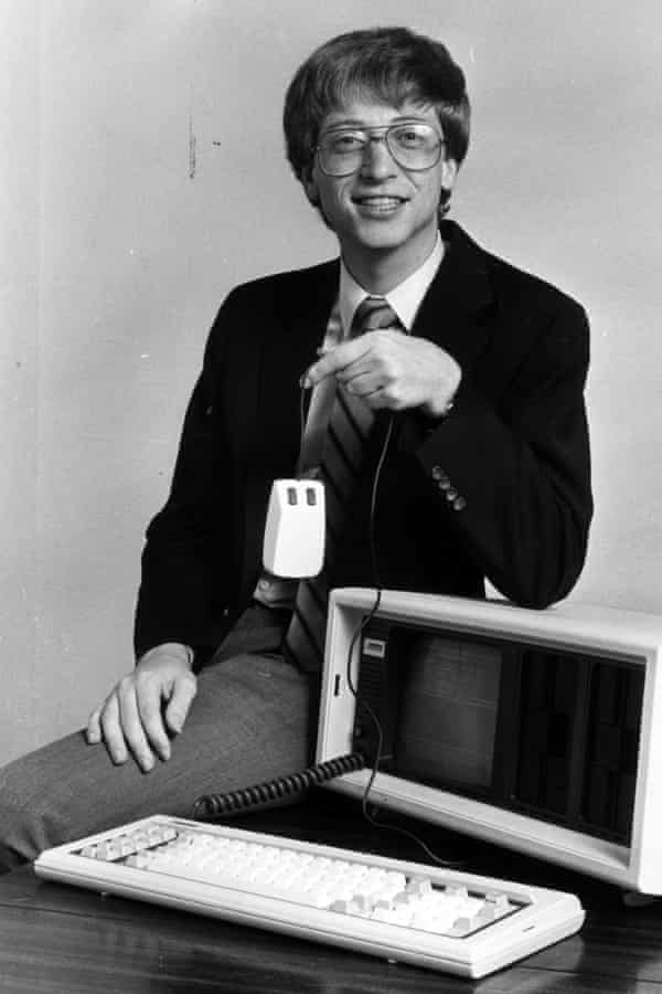 A young and smiling Bill Gates perched on a desk with a computer on it
