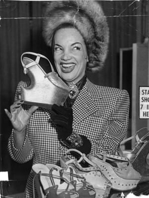 Carmen Miranda holds one of her newly designed evening shoes, which has a 7-inch heel.