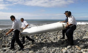 Officers carrying a flaperon from MH370.