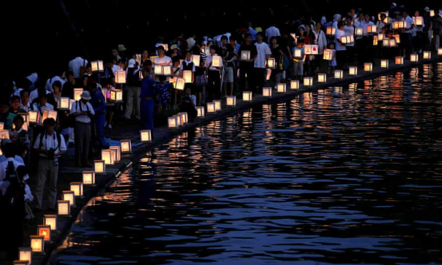 People carry paper lanterns to release onto the Urakami River for peace and the atomic bomb victims as they walk along the river in Nagasaki, Japan.