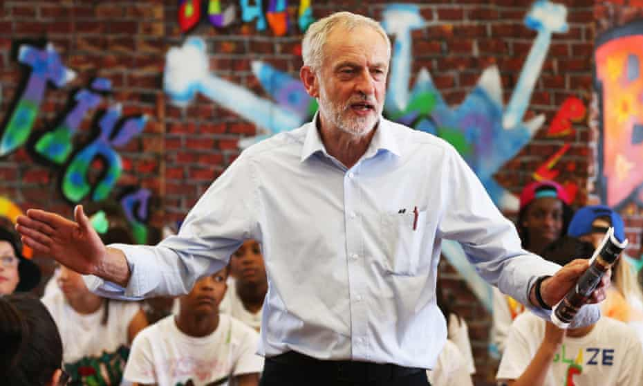 Labour leadership contender Jeremy Corbyn presents pupils with certificates after they perform in a play on their last day of school.