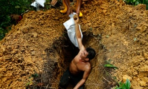 A grave digger hands over coffin nails while exhuming a grave at Bukit Brown Cemetery, Singapore.