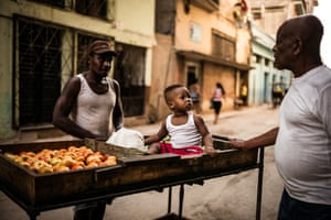 A young boy sits in the tomato section of his father s cart, as they both work on the sale, Havana