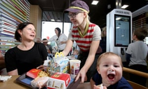 Carla Rogers delivers food to Jenny Wilson and her son Ted at the McDonald's at Hyde, in Greater Manchester.