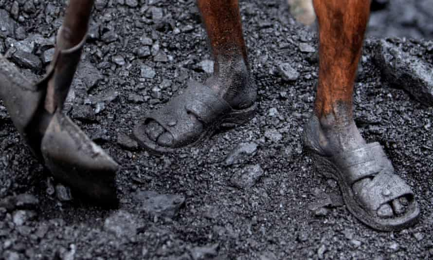 An Indian labourer works at a coal depot on the outskirts of Jammu, India.