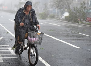A cyclist braves the wind and rain in Taipei.