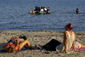 Tourists lie on a beach as migrants arrive on a dinghy at the Greek island of Kos after crossing a part of the Aegean Sea between Turkey and Greece, August 8, 2015.   The U.N refugee agency, UNHCR, estimates that Greece has received more than 107,000 refugees and migrants this year, more than double its 43,500 intake of 2014.