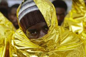 A migrant waits to disembark from a Coast Guard ship in the Sicilian harbour of Messina, Italy. Around 300 migrants were taken to safety in the Sicilian port of Messina after being rescued at sea near Libya. The migrants from Sub-Saharan Africa had been rescued on Monday after travelling on two dinghies sailing towards Europe.