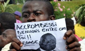 A man holds a picture of Accrombessi reading 'Beninese Accrombessi, get out!'.