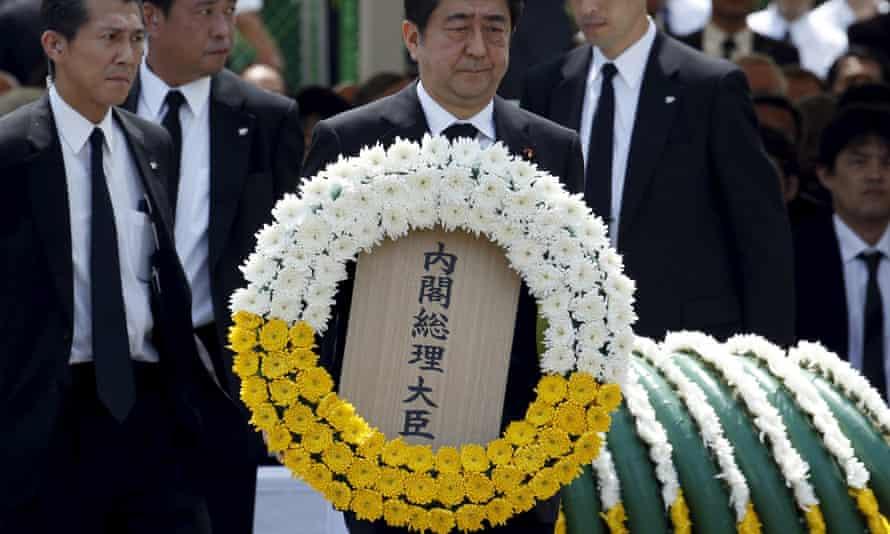 Shinzo Abe carries a wreath at the Nagasaki memorial.