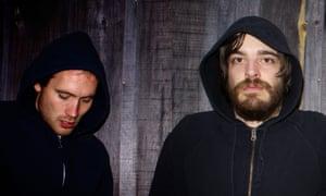 The band members of Holy Fuck, wearing dark hoodies
