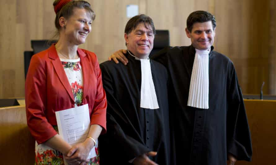 Urgenda Foundation director Marjan Minnesma, left, and lawyers Koos van der Berg, center, and Roger Cox, right, pose for pictures after a Dutch court ordered the government to cut the country's greenhouse gas emissions by at least 25% by 2020.