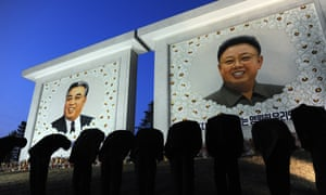 Koreans pay their respects in front of two portraits, in 2012.