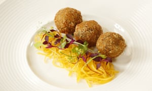 Three golfball-sized balls of haggis next to shredded turnip topped with delicate violet petals