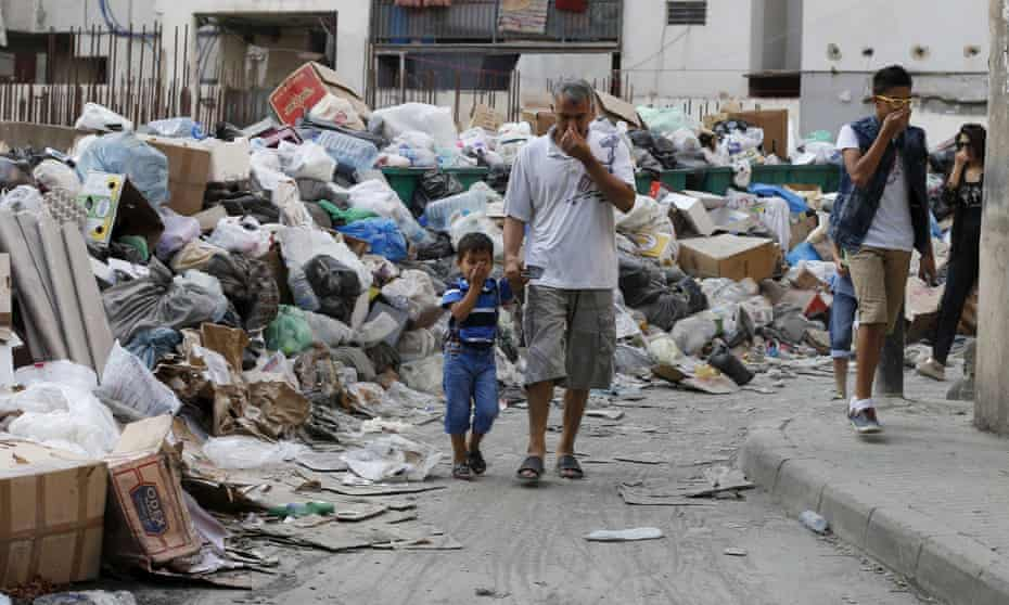 Residents cover their noses as they walk past garbage