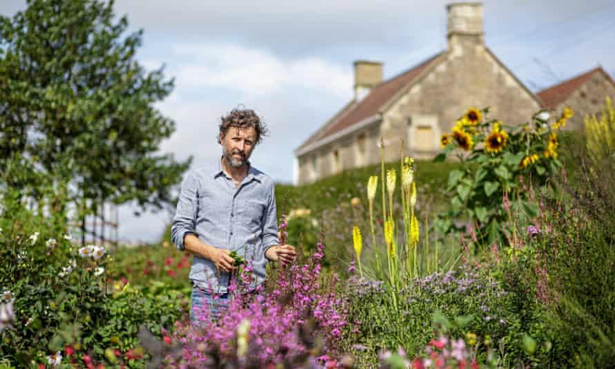 Dan Pearson, bearded, squinting, standing in his farm's flower garden