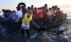 A Syrian child smiles as a group of refugees arrive on the Greek island of Kos