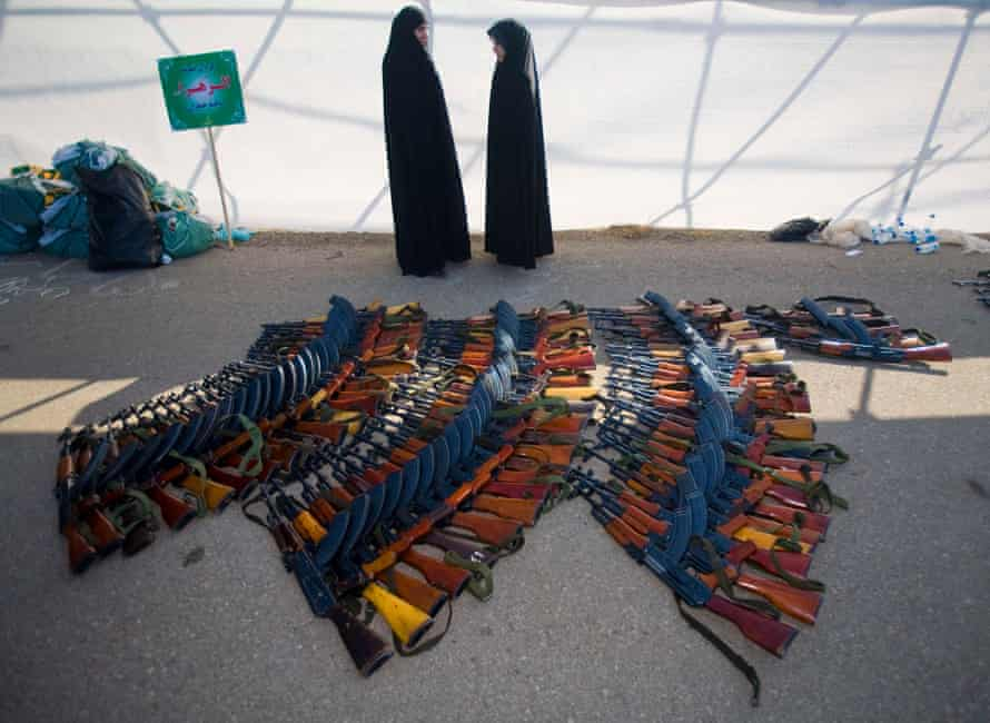 Members of the Basij militia's Alzahra battalion stand next to assault rifles after a military parade to mark Basij week at a Revolutionary guard's military base in northeastern Tehran November 25, 2008.