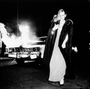 Patti Hansen, in finery of gown, fur coat and hair do, walks away from a burning car. This is glamour augmented with cinematic drama.