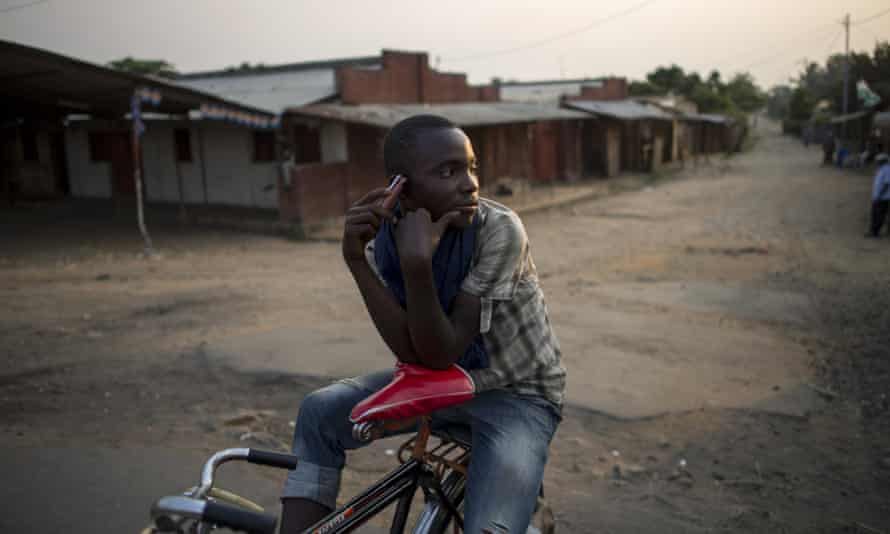 A bicycle taxi-man listens to the news using the radio on his mobile phone while waiting for clients in Bujumbura, Burundi.