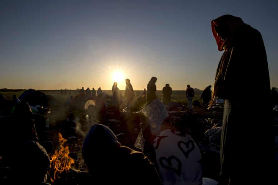 Refugees stand around a fire in a makeshift camp at a collection point in the village of Röszke, Hungary. Photograph: Marko Djurica/Reuters