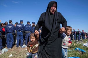 Police surround refugees, many from Syria, on the Serbian-Hungarian border. Photograph: Antonio Olmos