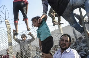 A Syrian child fleeing the war is lifted over border fences to enter Turkish territory illegally, near the Turkish border crossing at Akçakale in Sanliurfa province. Photograph: Bulent Kilic/AFP/Getty Images