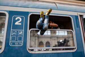 A boy is pulled through the window of a domestic Hungarian train. The refugees were later forced to get off the train by Hungarian police after all international trains were cancelled.