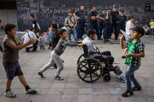 A young boy pushes a disabled relative while around them children play.