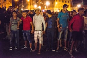 Refugees hold hands to form a protective barrier after some football hooligans and fascists showed up at Budapest and jeered at the refugees.