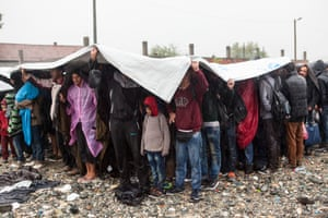 Refugees at the UNHCR Registration centre in Gegeliya wait to board a train that will take them to the Serbia border with Macedonia. The boarding was chaotic as it poured down with heavy rain.