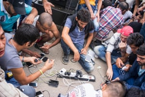 People charge their phones on a power outlet connected to a generator at Eidomeni, a Greece Border crossing