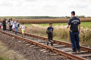A policeman stops Refugees at Roszke Crossing on the Serbian-Hungarian Border.