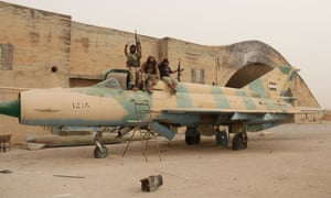 Fighters affiliated to al-Qaeda sit on a Syrian warplane after they seized the Abu Duhur military airbase in the northwestern Idlib province, on 9 September 2015.