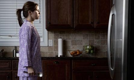 woman in pyjamas looking at the fridge