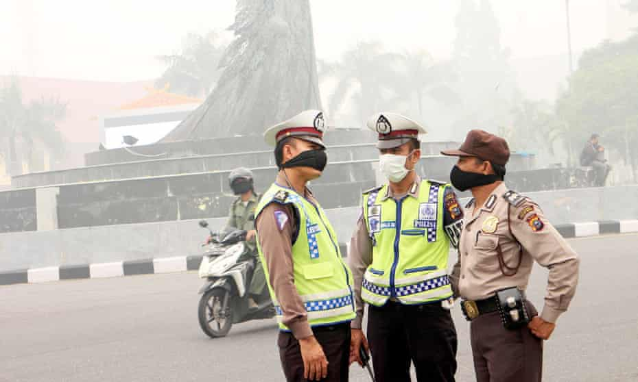 Indonesian police wear masks against the smoke from forest fires.