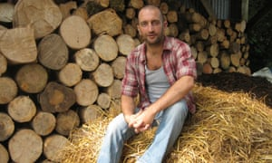 Mark Boyle (moneyless man) sitting on hay bale