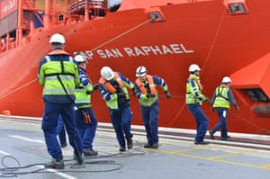 Dockers tie up a ship.