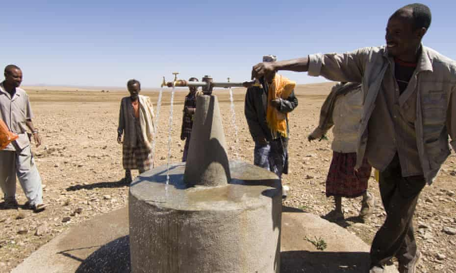 A man turns on a water tap in the dessert