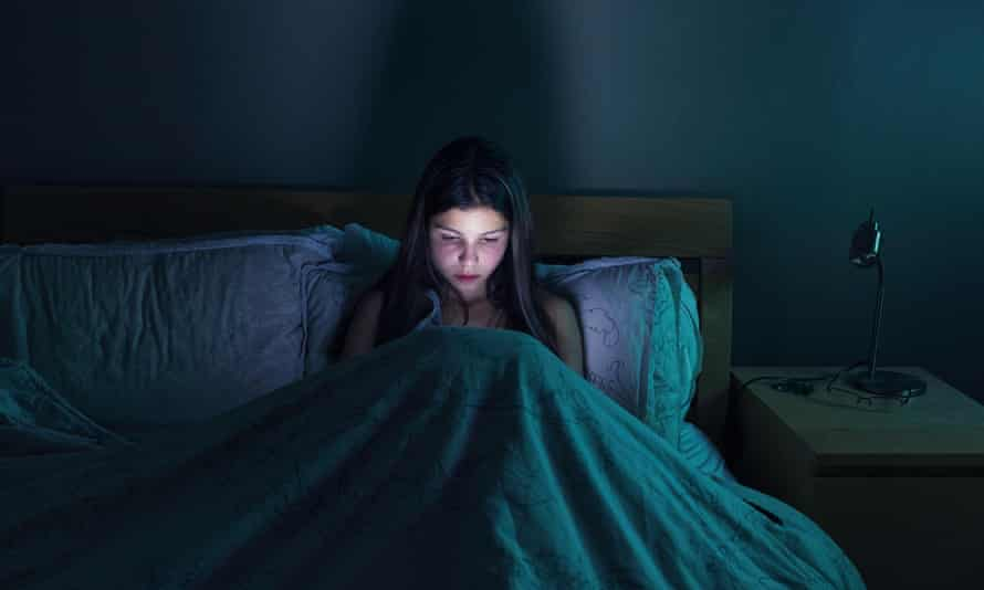 Girl using her mobile phone in bed