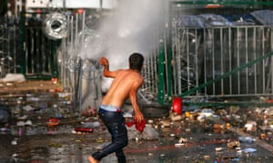 A migrant protests as Hungarian riot police fires tear gas and water cannon at the border crossing with Serbia.